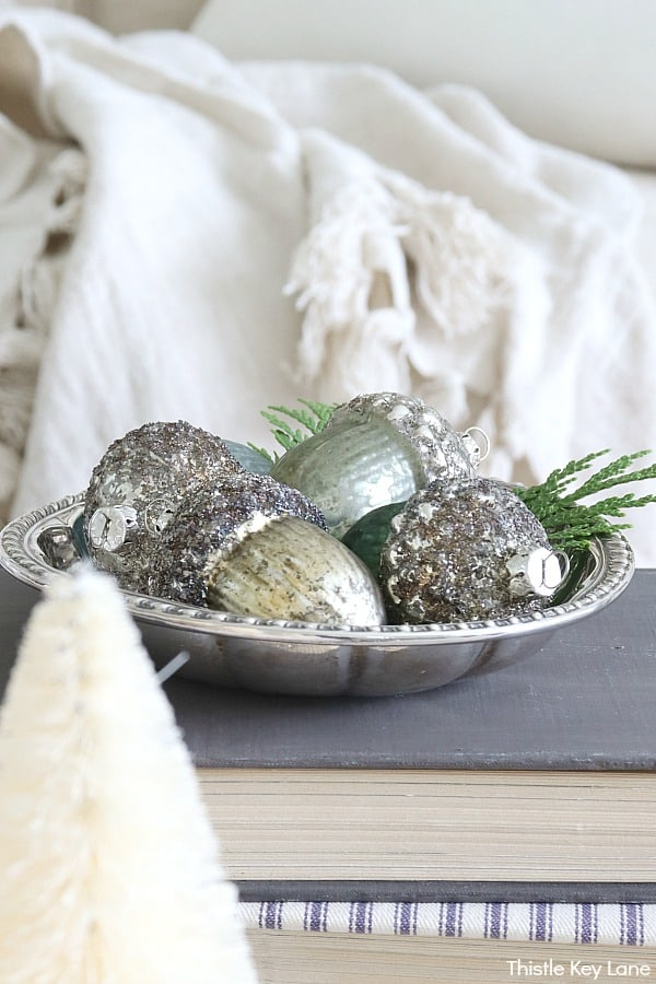 Silver bowl with vintage ornaments on books next to white bottle brush trees.