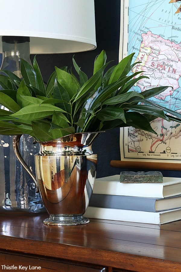 Silver pitcher with green leaves.