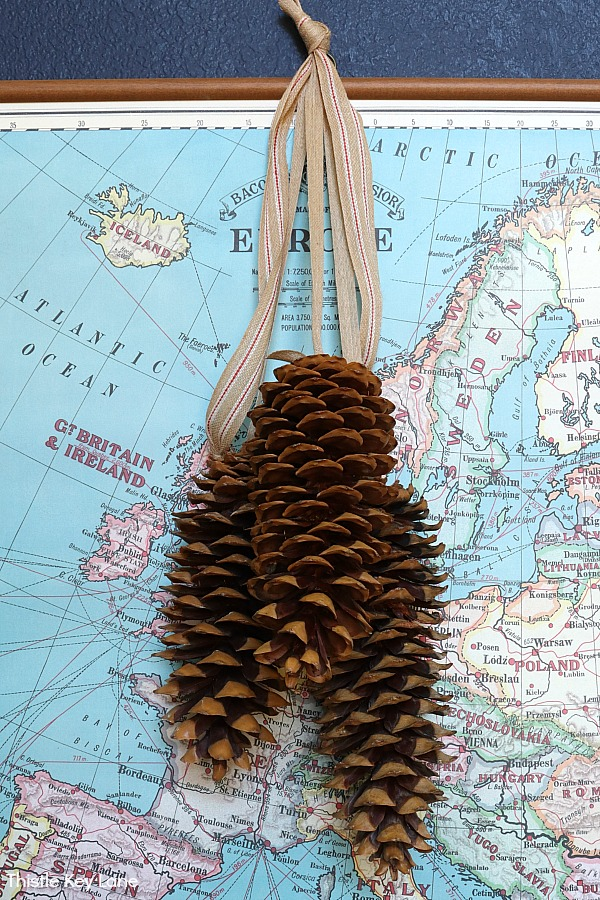 Pinecone swag hanging over a map. Winter Entry Table And A Pinecone Swag.