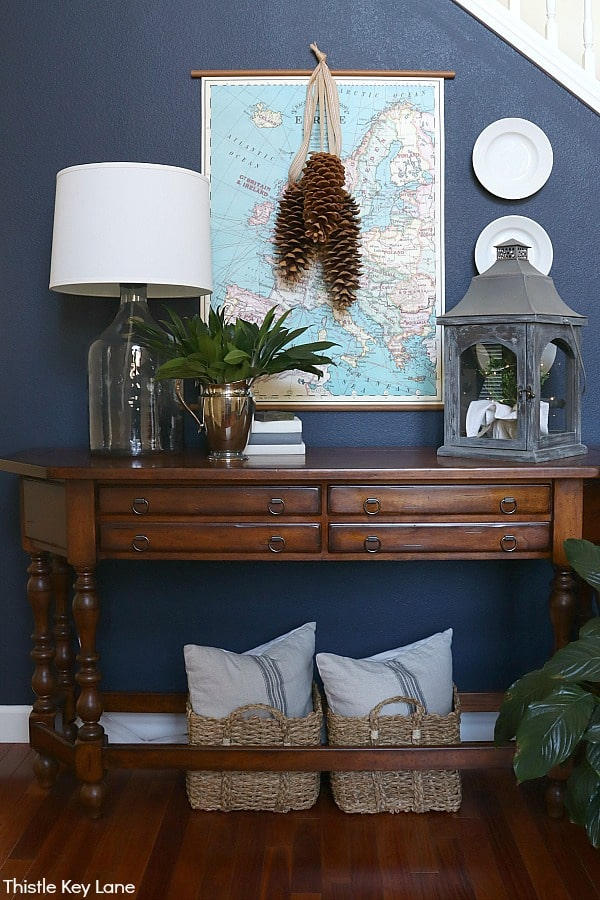 Entry table with map and baskets under holding pillows. Winter Entry Table And A Pinecone Swag.