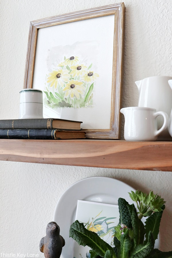 Botanical watercolor and white ironstone creamers on a shelf.