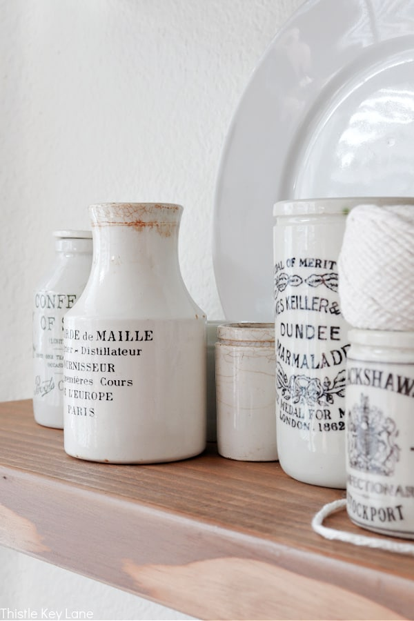 Ironstone jars of different sizes on a shelf.