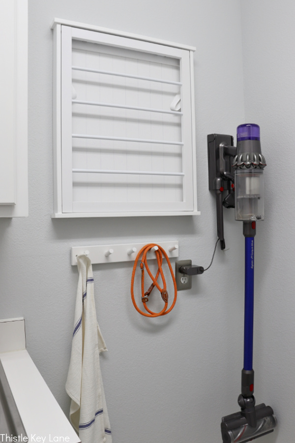 Drying rack and cordless vacuum on laundry room wall. Laundry Room Organizing Ideas
