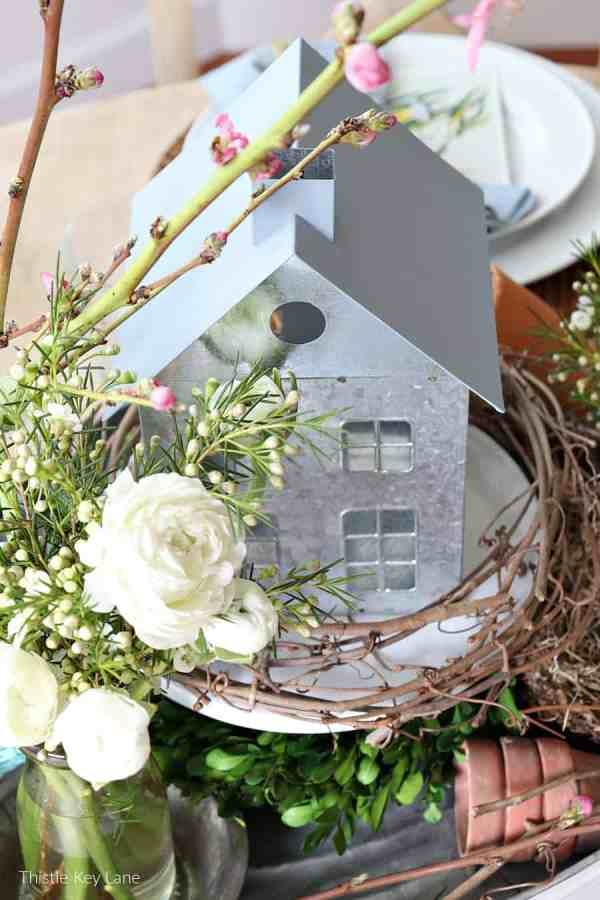 Spring arrangement on a tray with metal house and flowers. Spring Bird Theme Inspired Centerpiece.