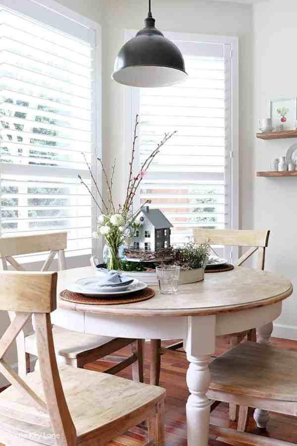 Kitchen table in front of white shuttered windows.