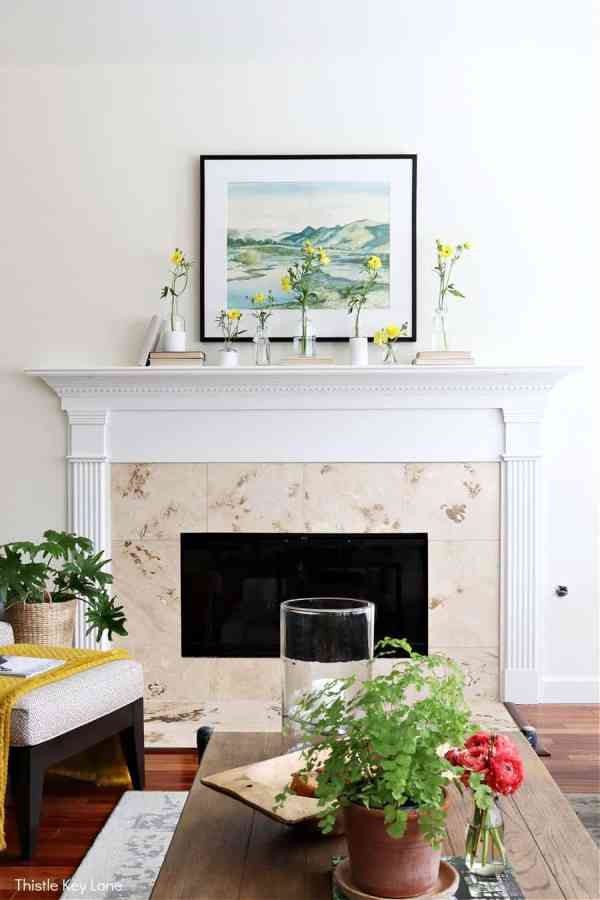Fireplace mantel with neutral colored books and flowers. Spring Mantel With Flowers And Bottle Vases.
