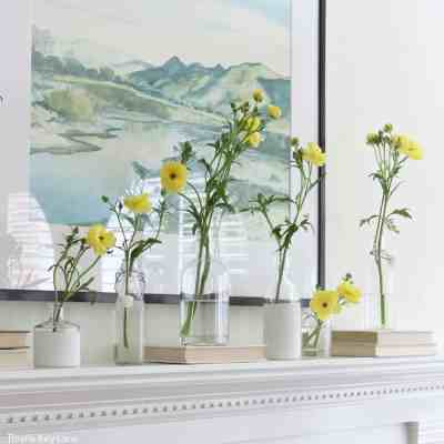 Spring Mantel With Flowers And Bottle Vases