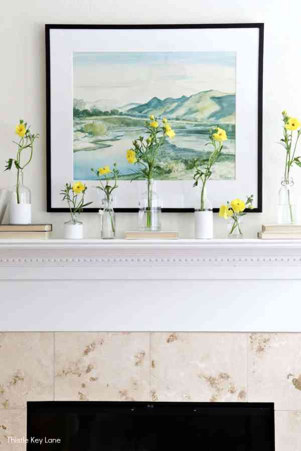Spring mantel with flowers and bottle vases with landscape watercolor.