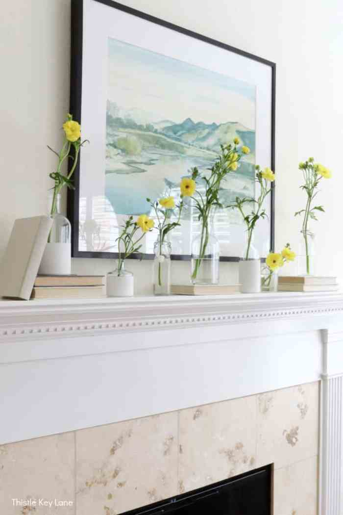 Bottles holding flowers sitting on books on the mantel. Spring Mantel With Flowers And Bottle Vases.