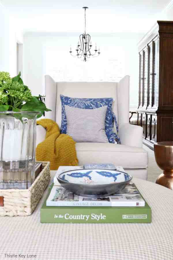 Ottoman with blue accents and a chair with blue and white pillows - Decorating With Hints Of Blue.