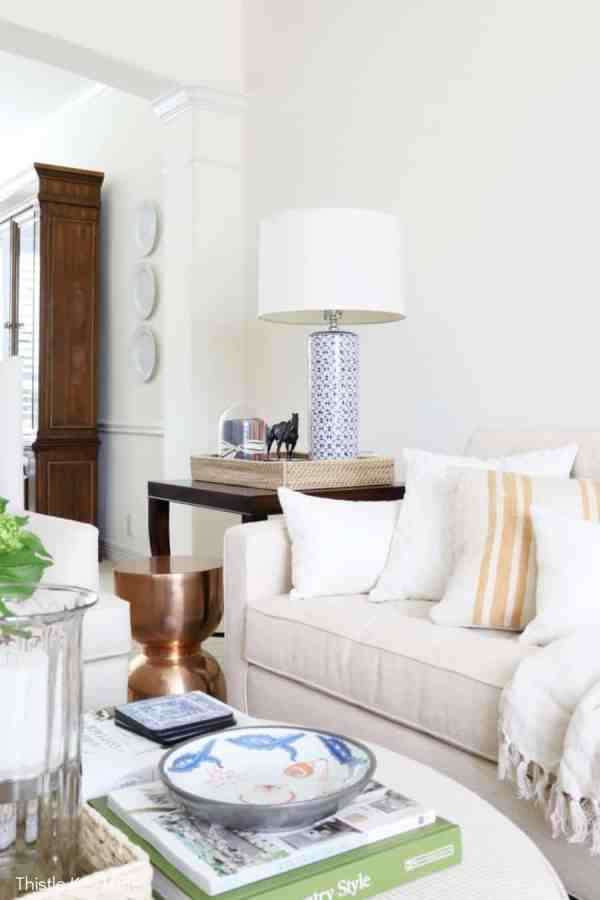 Blue and white lamp sitting between neutral colored furniture. Decorating With Hints Of Blue.