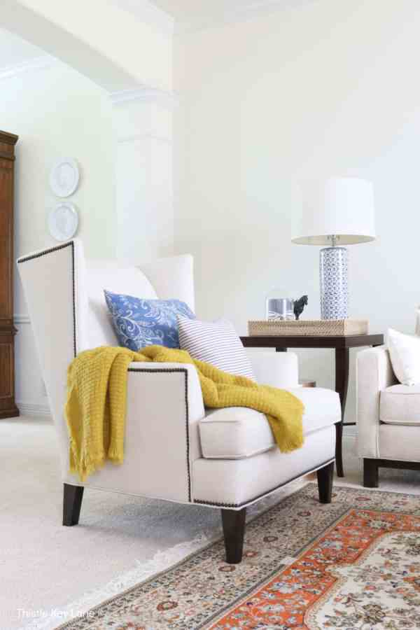 White wing back chair with blue pillow and yellow throw. Decorating With Hints Of Blue.