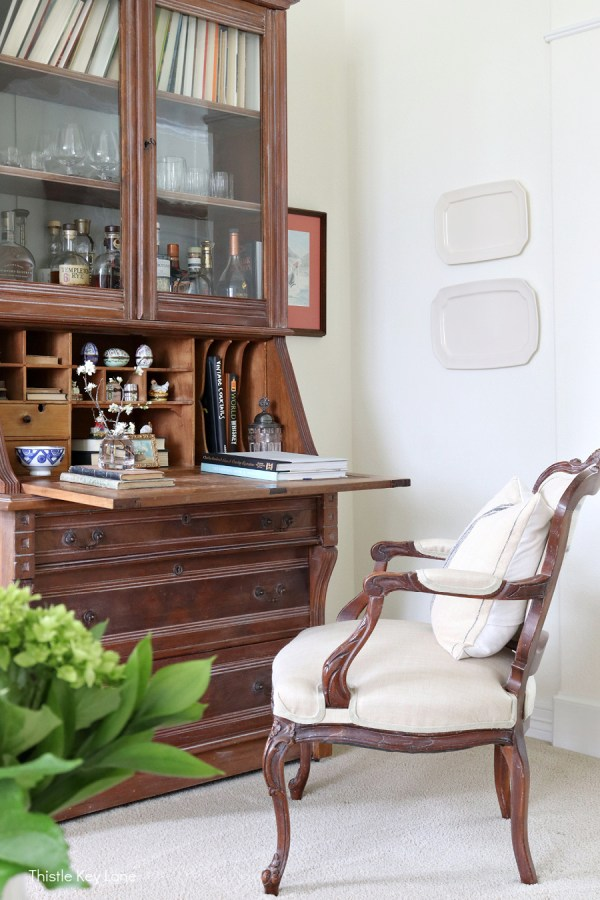 Secretary desk used as a liquor cabinet and for displaying a small collection.