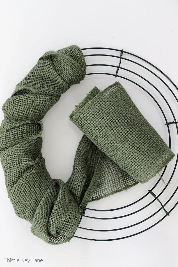 Green burlap ribbon wrapped around wire wreath frame.