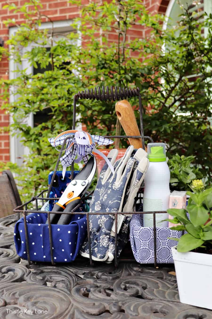 Garden gloves, pruning clippers, and other supplies in a wire caddy. DIY Garden Tool Caddy.