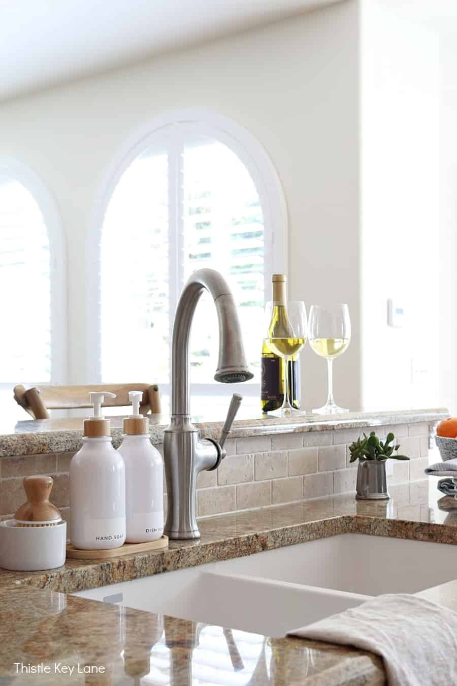 Kitchen sink, white soap bottles, big windows in background.