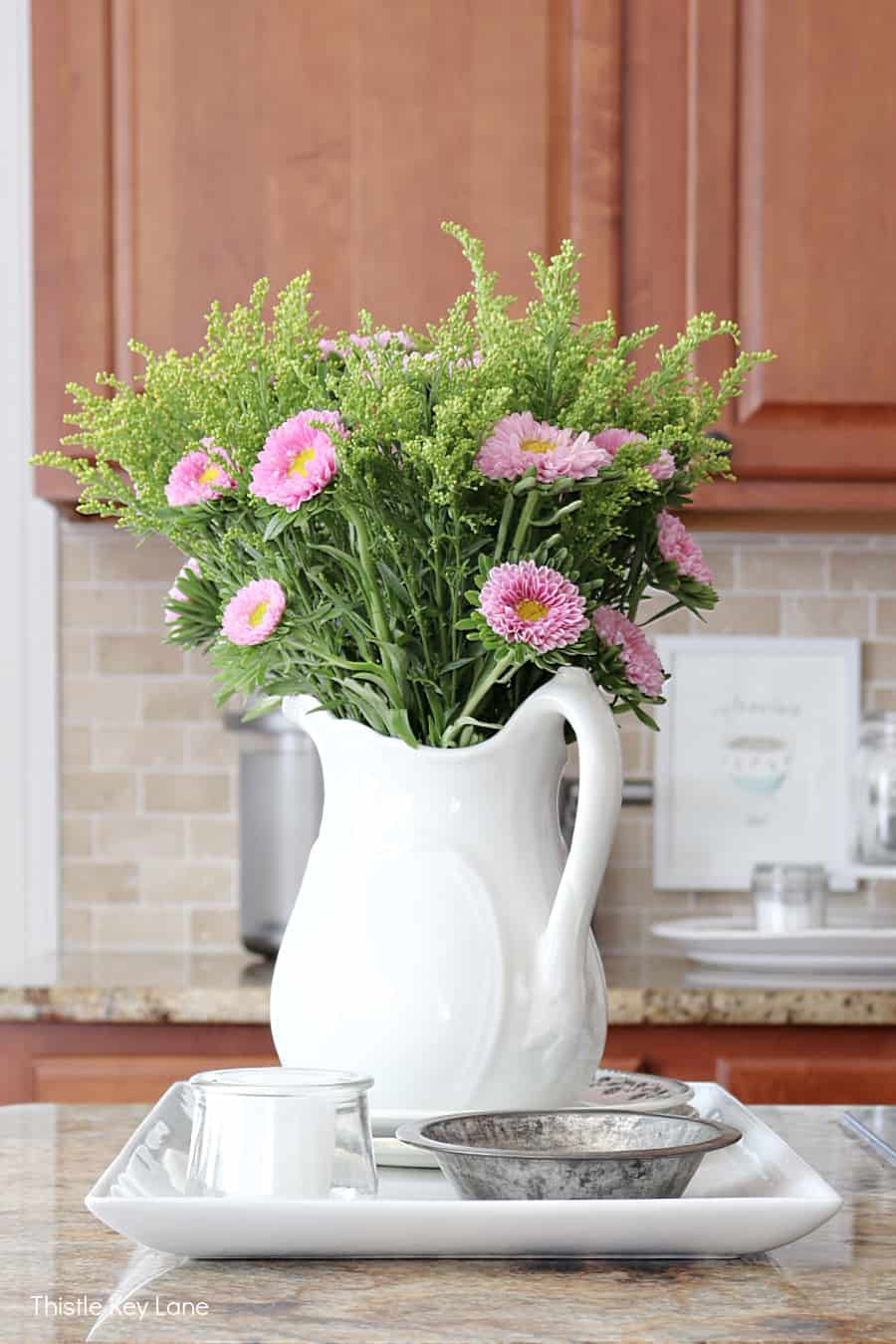 White ironstone pitcher with pink asters and greenery - Using Trays To Control Kitchen Clutter.