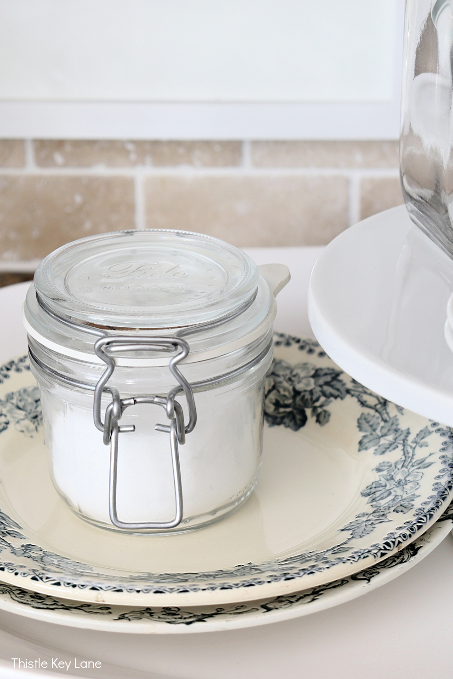 Vintage blue and white plates with a jar of sugar - Using Trays To Control Kitchen Clutter.