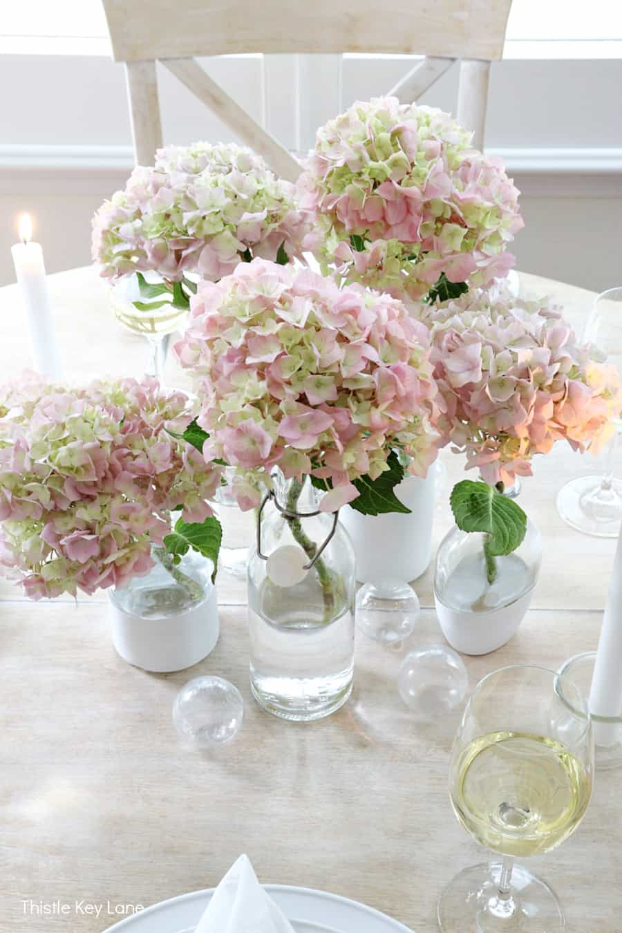 Overview of pink and green hydrangeas in the center of the table. Summer Tablescape With Glass Bottle Vases.