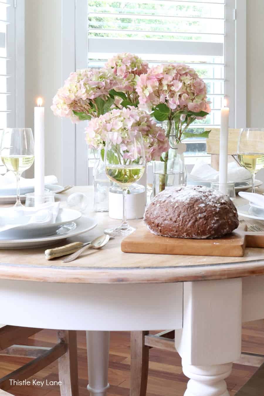 Tablescape with pink and green hydrangeas on a white and neutral table. Summer Tablescape With Glass Bottle Vase.