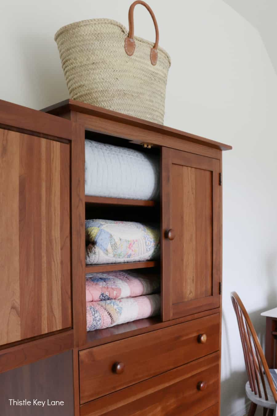 Armoire with quilts and a French market tote on top.