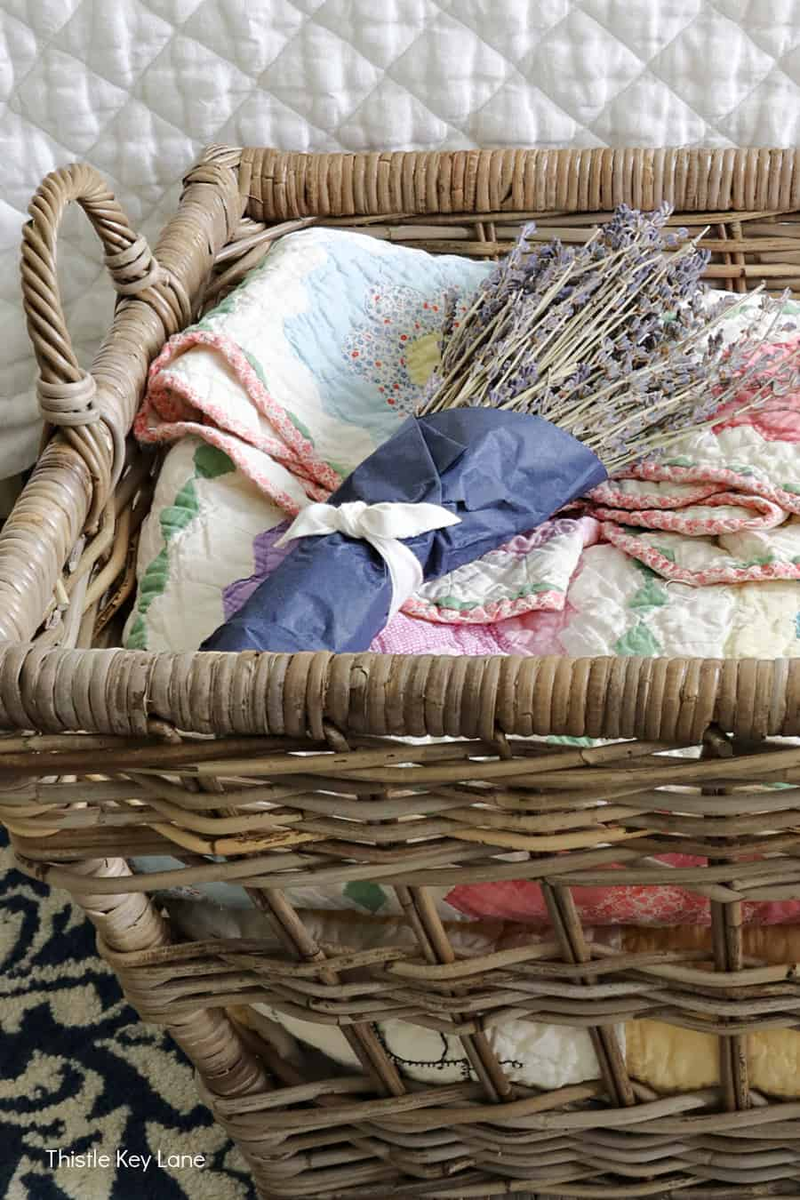 Basket with dried lavender sitting on quilts. Summer Bedroom Updates And A Quilt Basket.