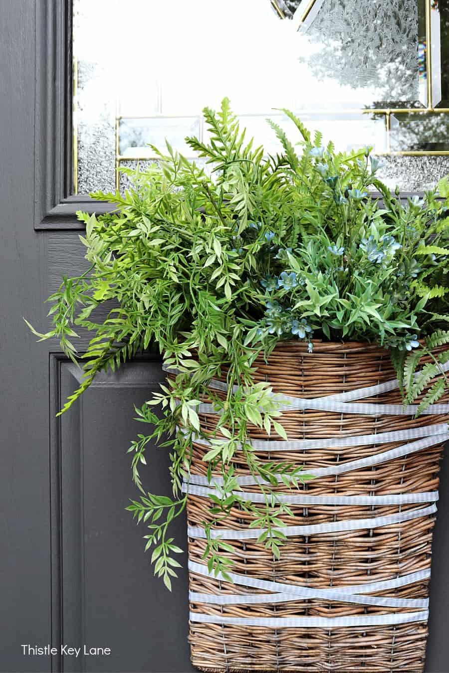 Summer front door basket with ferns.