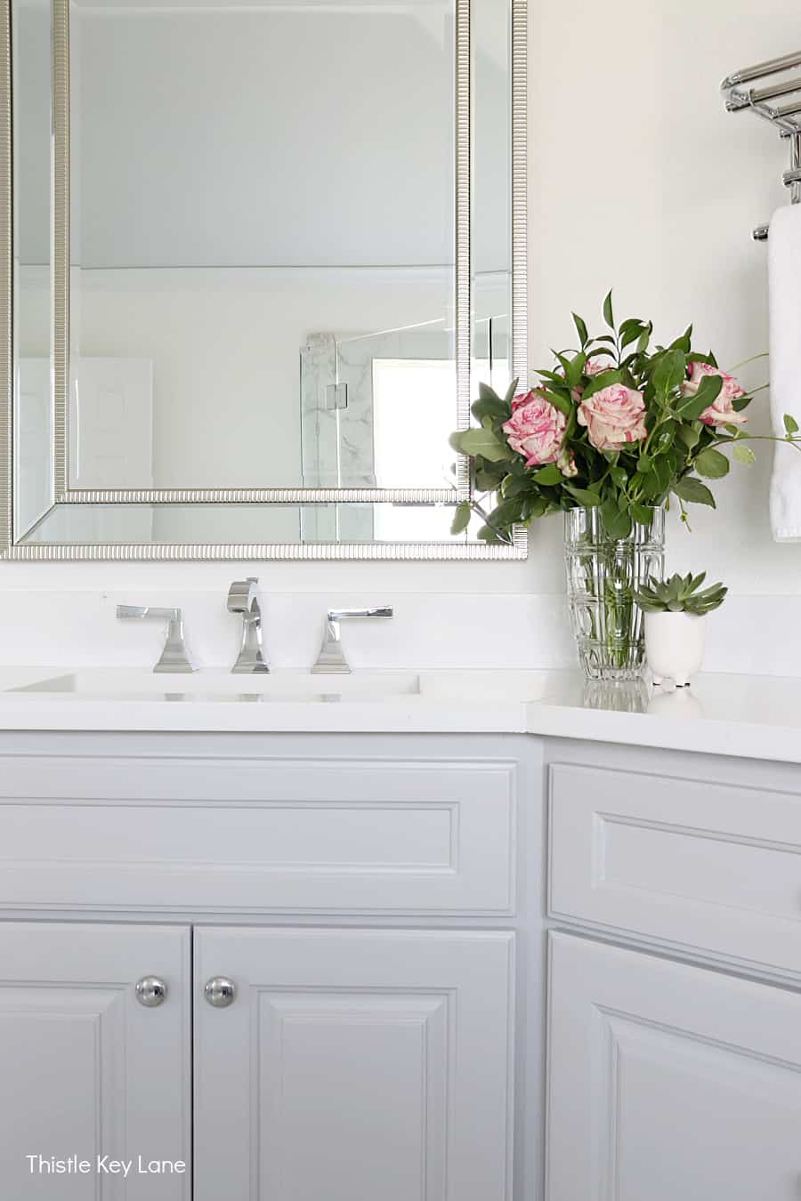 White quartz countertop, gray cabinets, pink rose arrangement. White And Gray Bathroom Makeover.