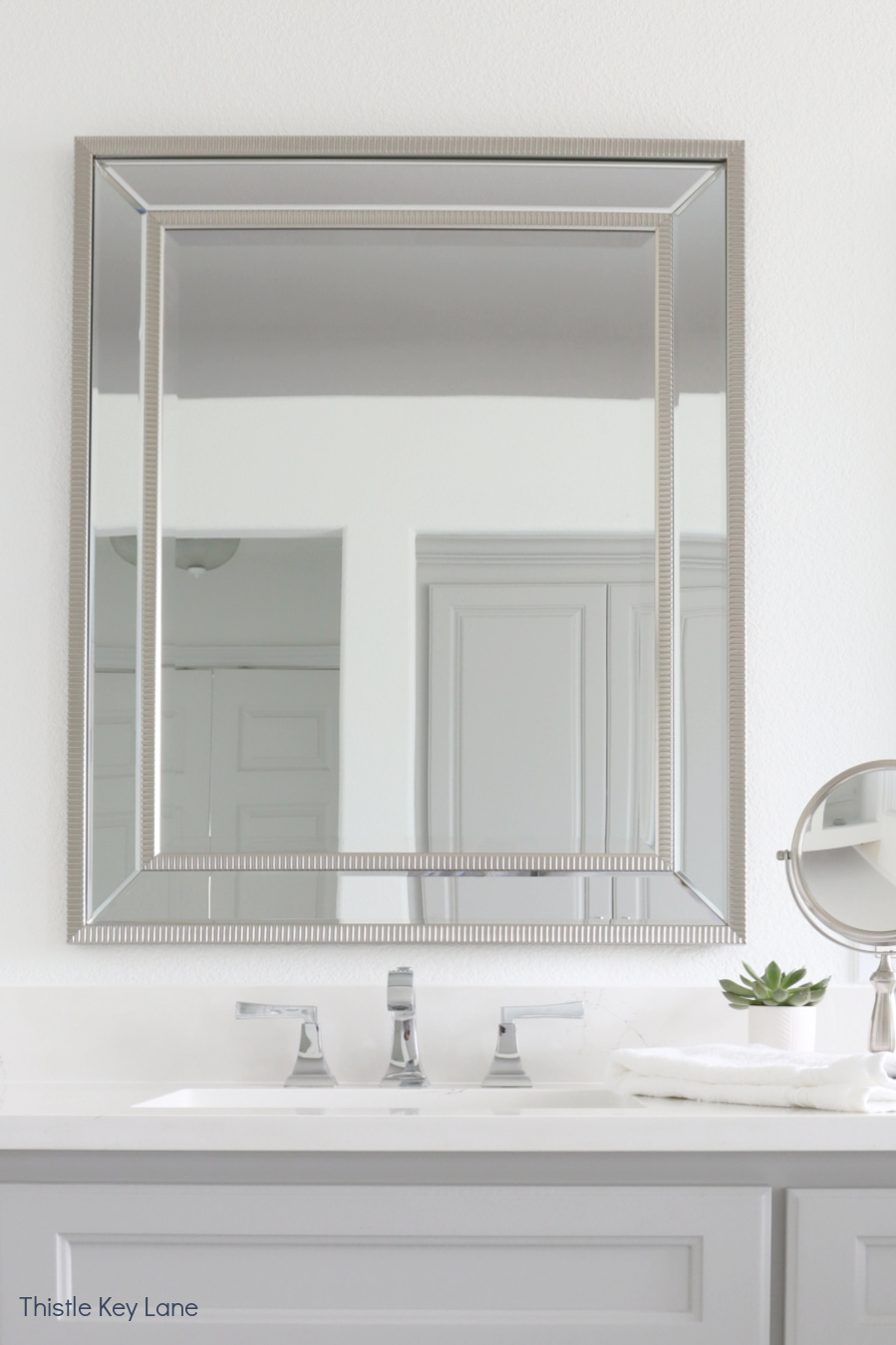 Brush finish mirror and sink. White And Gray Bathroom Makeover.