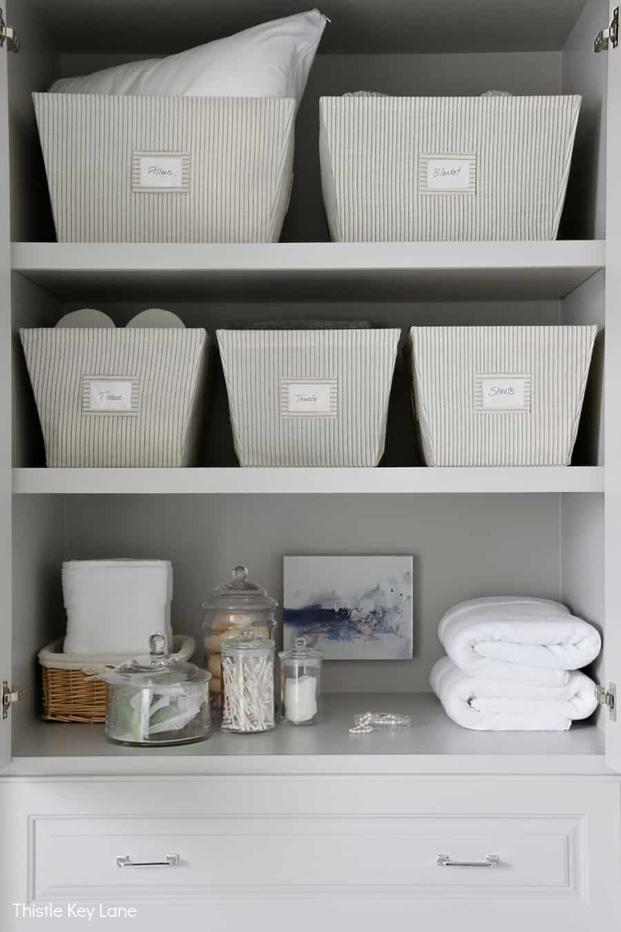 Shelves with bins and folded towels. Organizing A Master Bathroom Linen Closet.