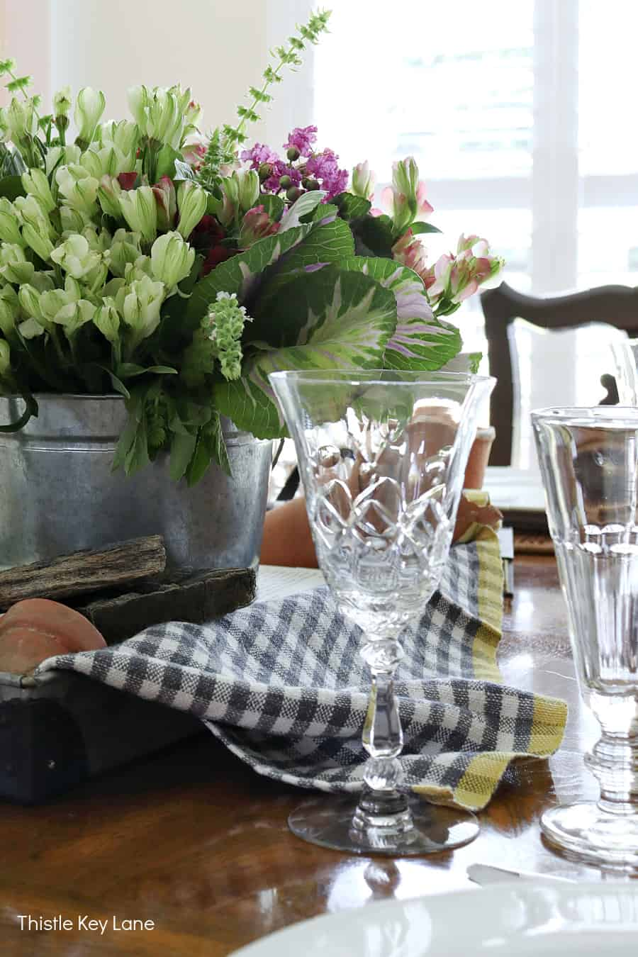 Crystal wine glass, gingham pattern and fresh flowers. Kale Flower Arrangement And Garden Tablescape.