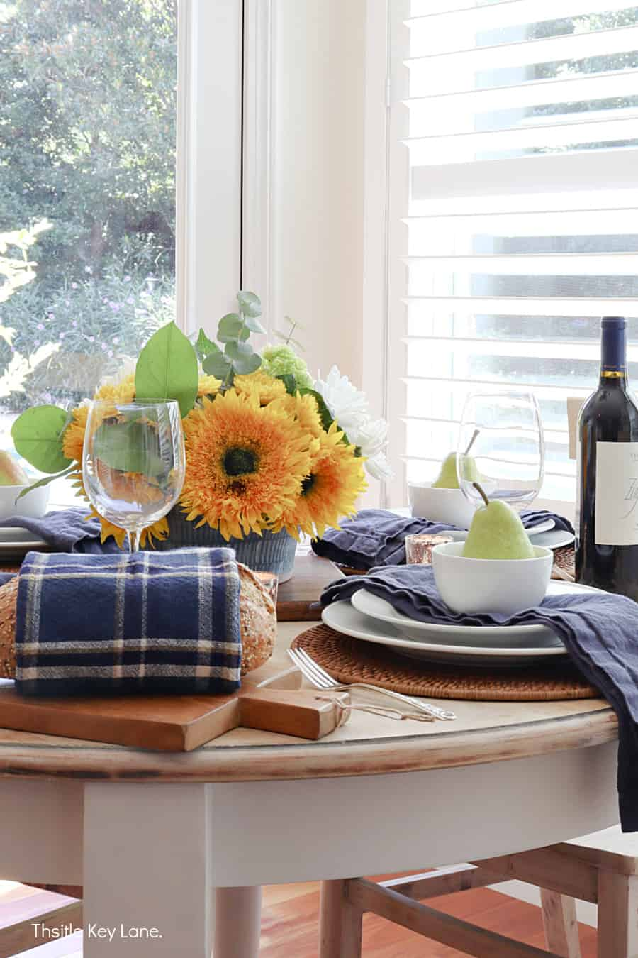 Sunflower centerpiece and navy accents. Early Fall Tablescape With Sunflowers.