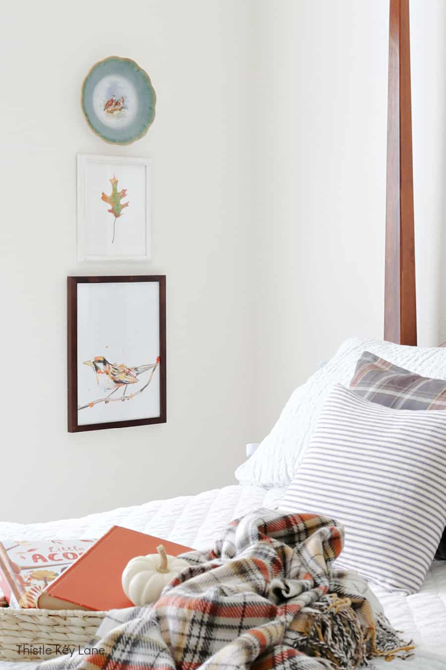 Decorative plate and framed artwork next to a bed.