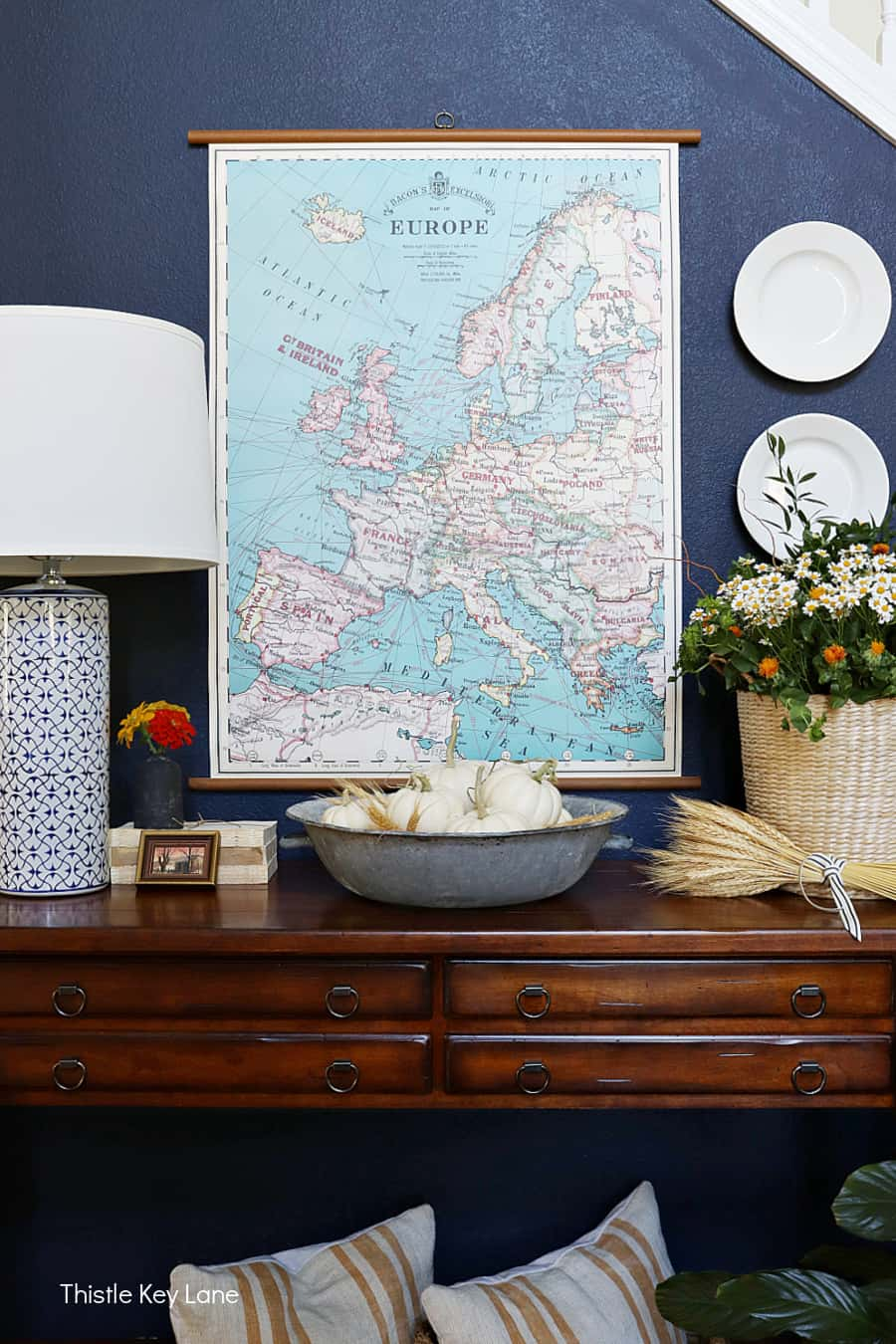 Entry table with pumpkins and flowers and a map on wall. Simple Fall Porch And Entryway Ideas.