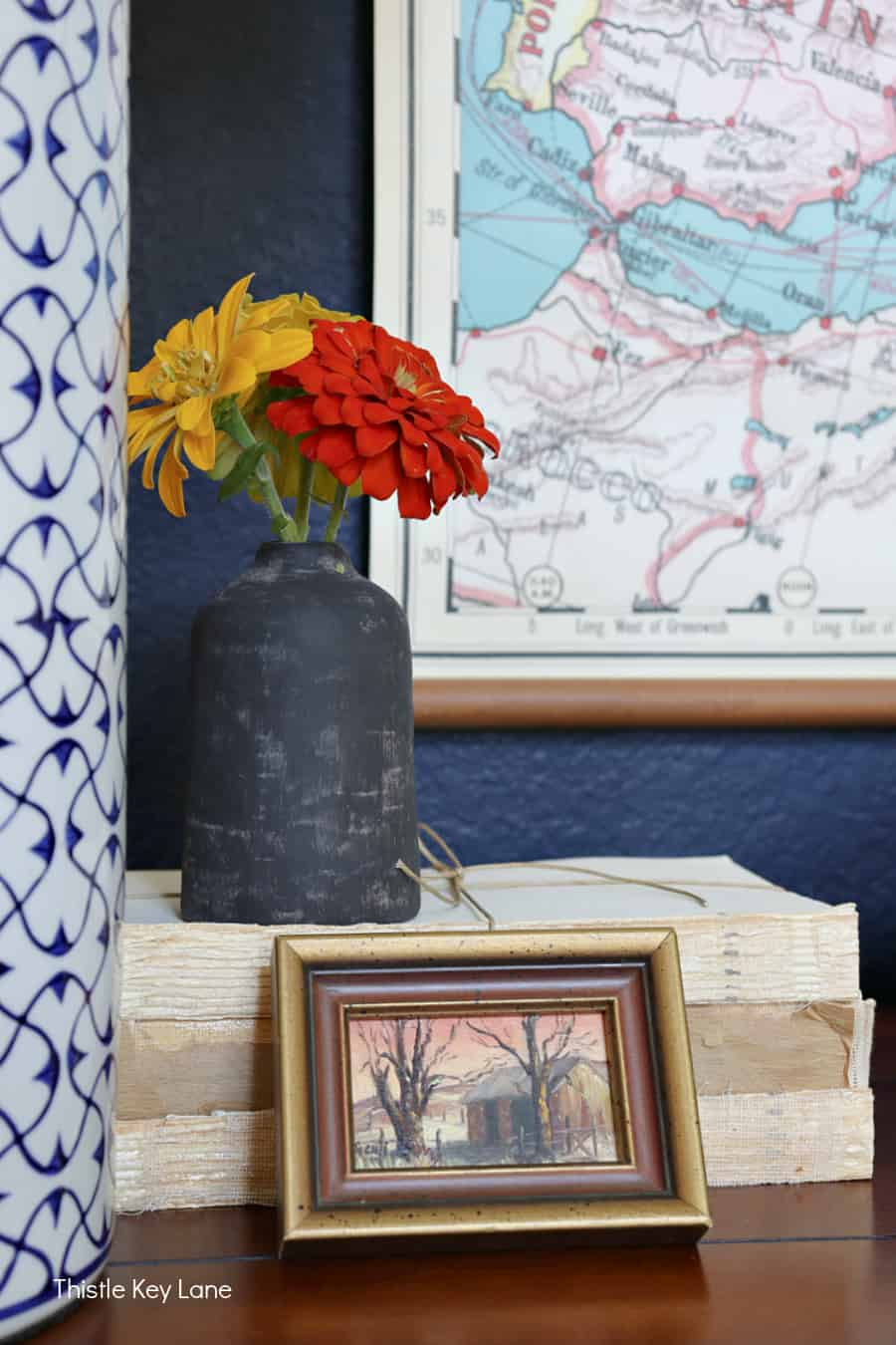 Zinnias in a black vase on books with a mini oil painting. Simple Fall Porch And Entryway Ideas.