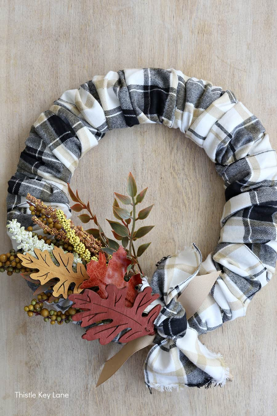 Black and white plaid wreath with light background. DIY Plaid Fall Wreath With Autumn Colors.