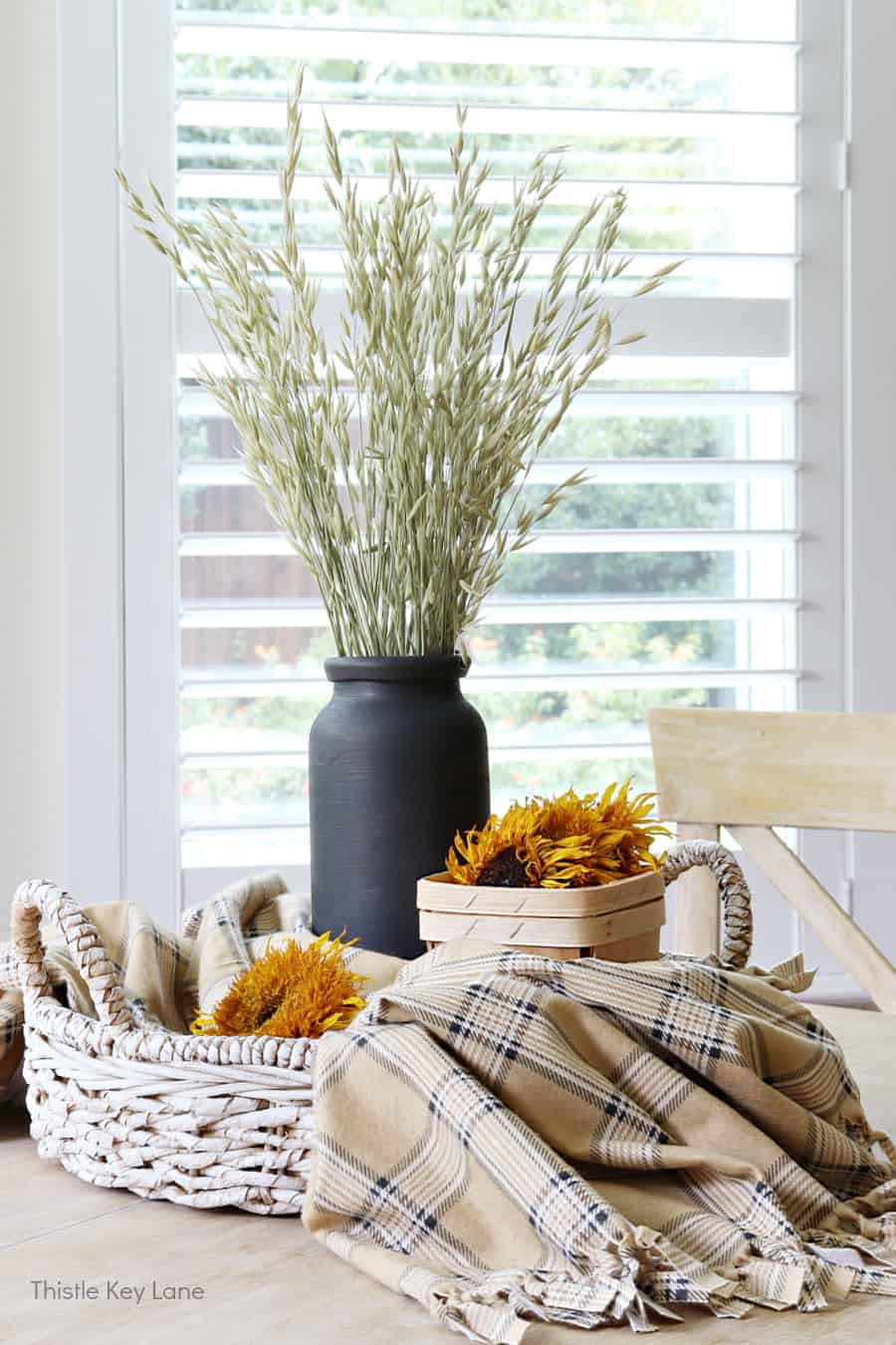 Round tray with plaid throw, dried grass in black vase, sunflowers in a basket. How To Make A Plaid Table Throw.