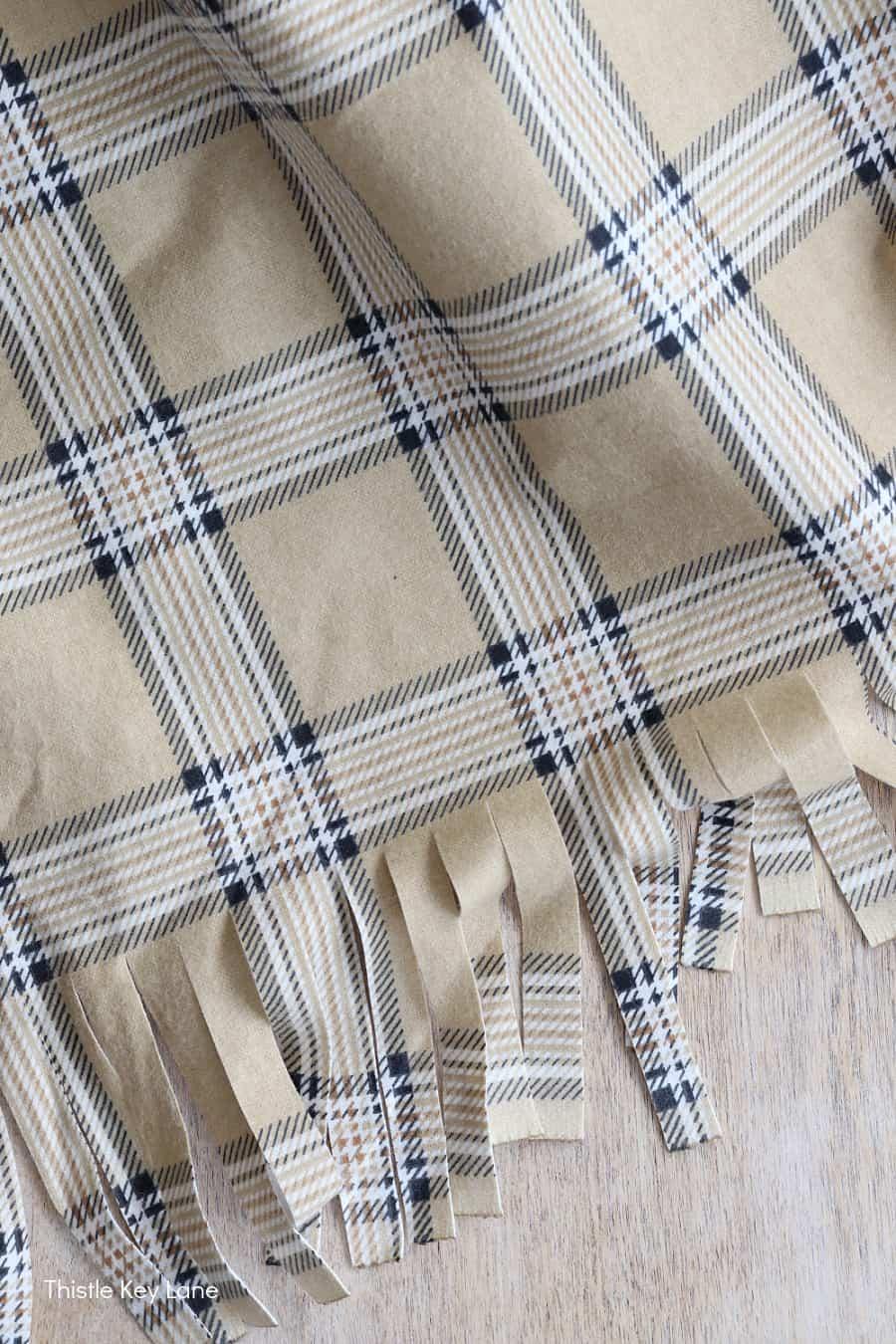 Plaid fabric with fringe cuts.