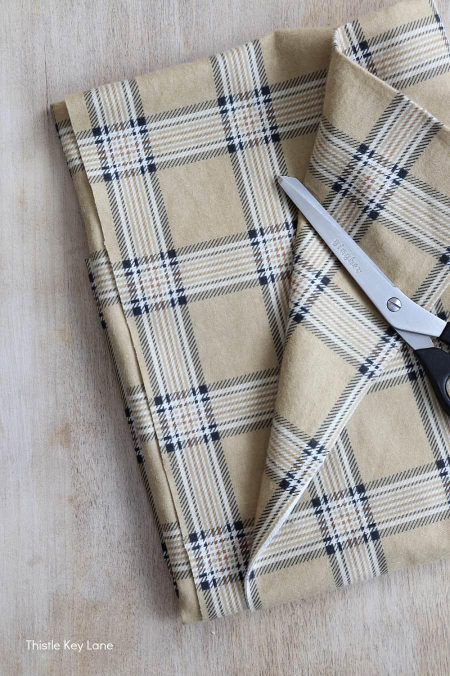 Plaid fabric with scissors.