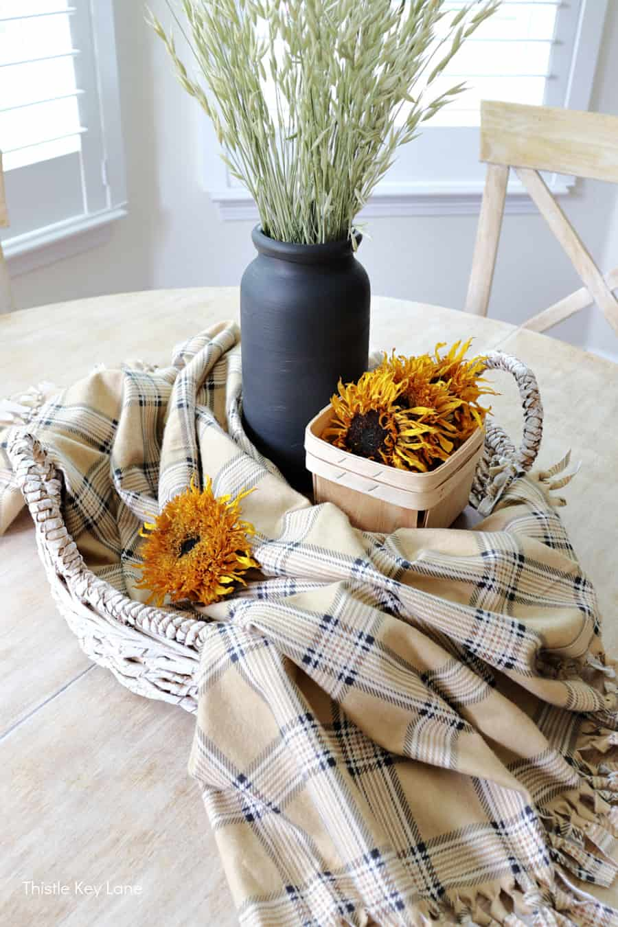 Plaid throw draped across a woven tray. How To Make A Plaid Table Throw.