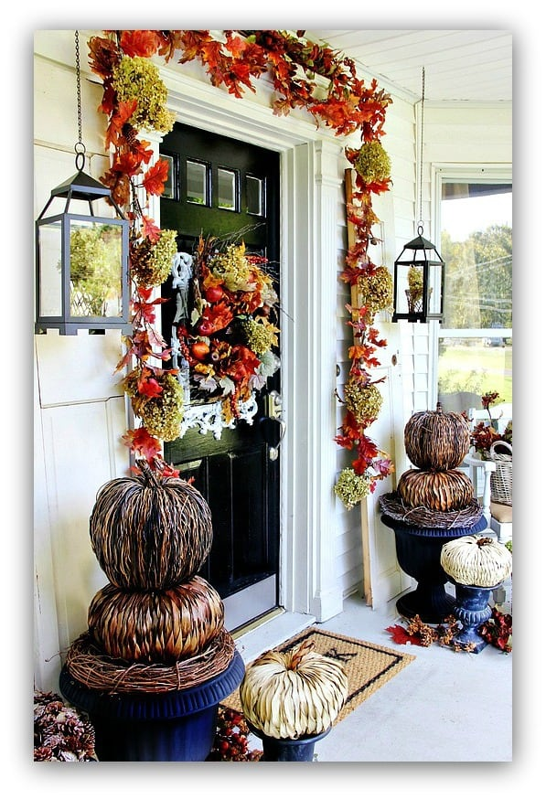 The autumn leaf garland and pumpkins add to the front door's fall decor.