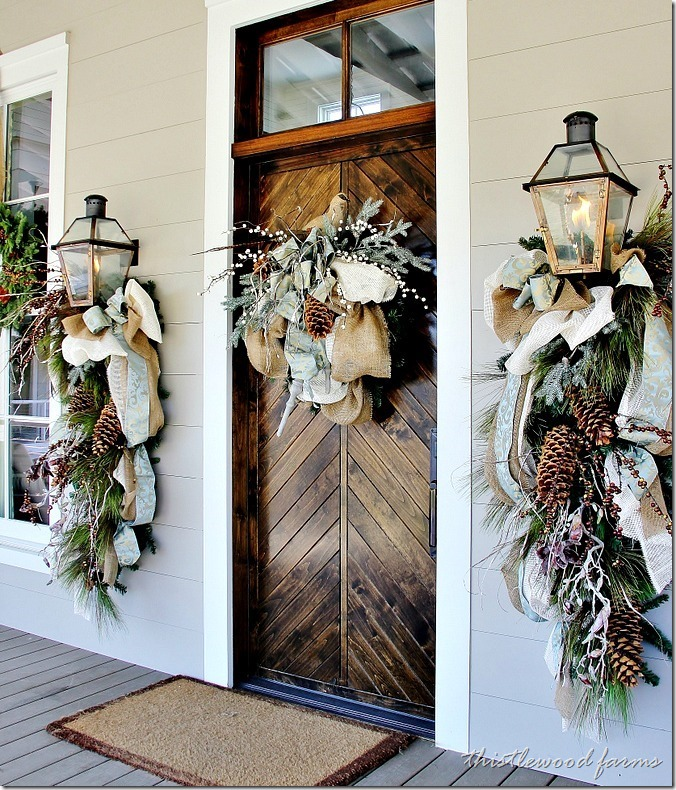 Southern style front porch from the Southern Ideas Home; large pinecone and greenery wreaths with twine and burlap ribbons