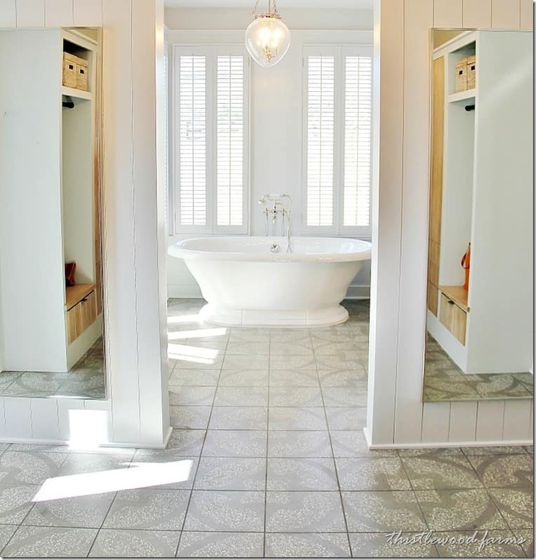 A wide open and bright master bathroom with a grand bathtub and closet space on each side