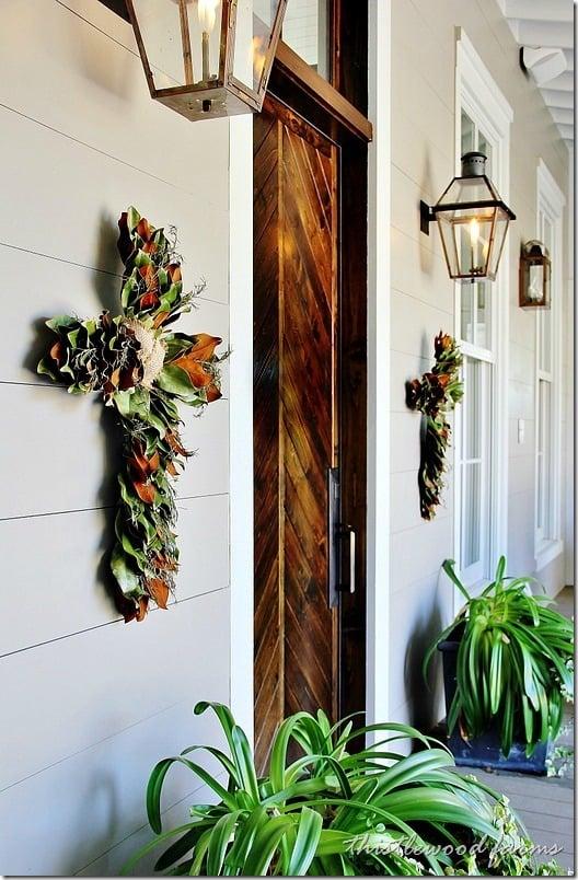 Vibrant magnolia flower crosses flank a dark barn wood front door