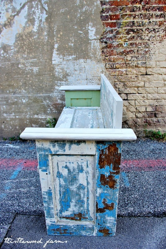 This bench is made from an old door and is detailed with rustic, chipped paint that gives it so much character