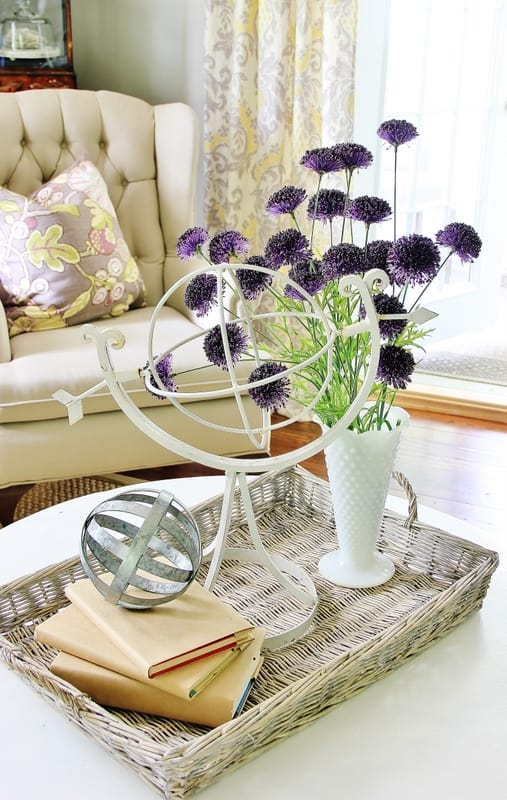 A white washed wooden tray decorated with books, a white vase with purple flowers, and a metal globe