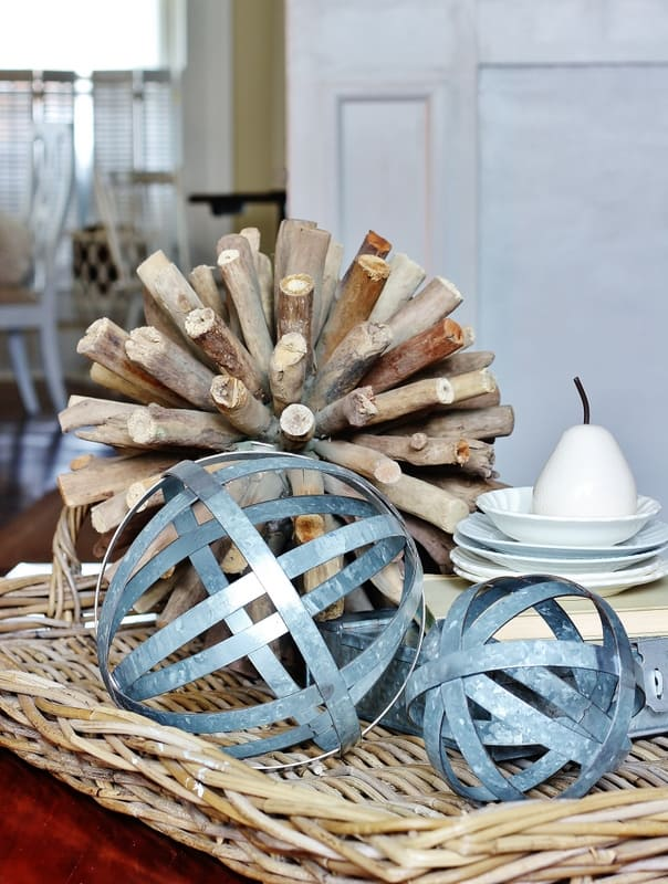 A woven wood try decorated with metal spheres and white dishes