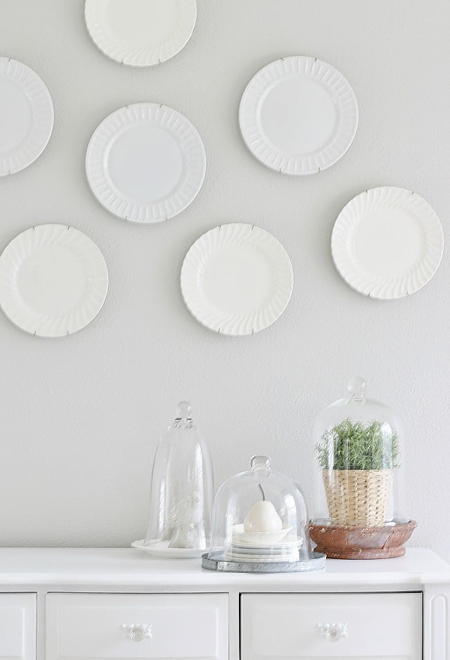 A painted gray wall with white plates and a soft white dresser