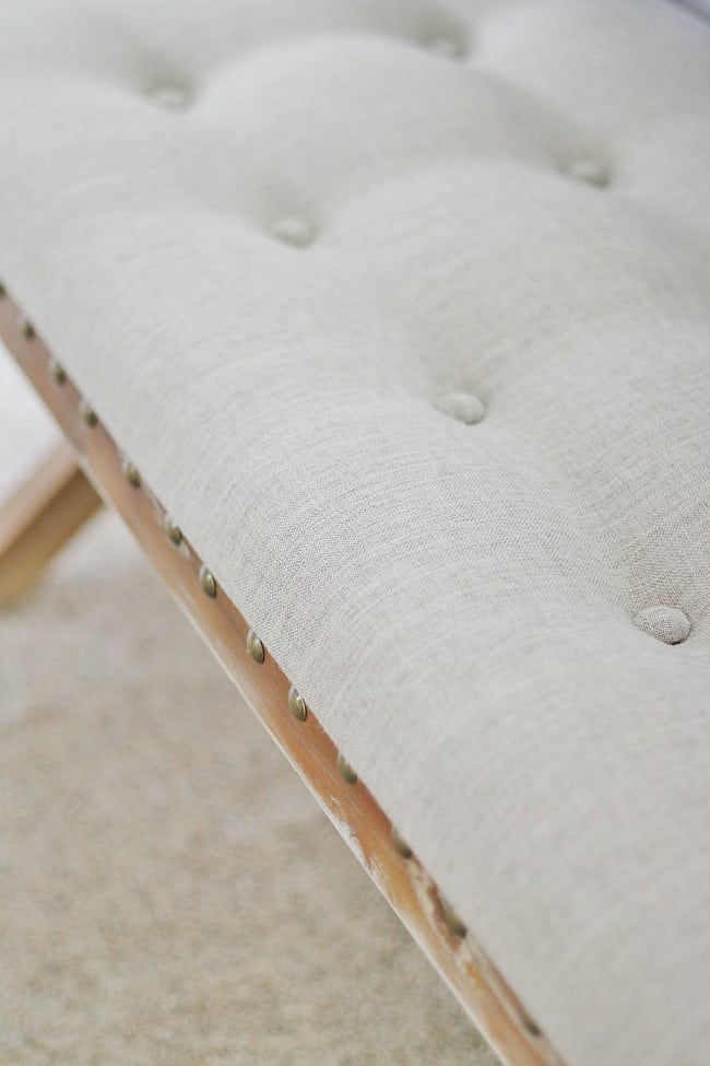 Light gray upholstered farmhouse bench with a wooden frame