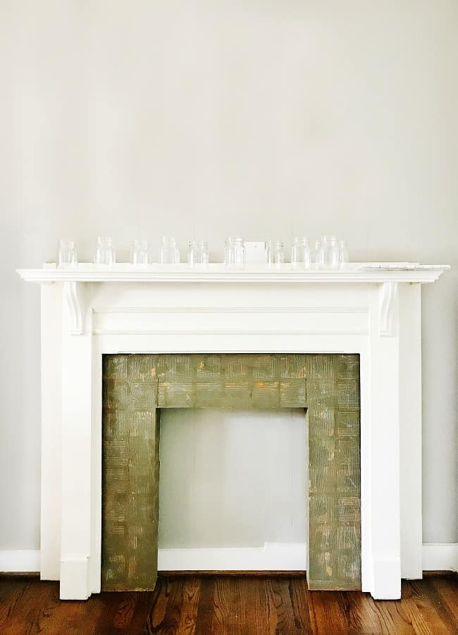 This white wood mantle needs an upgrade! The worn olive-green tiles lining the inside frame of the mantle are old and cracked.
